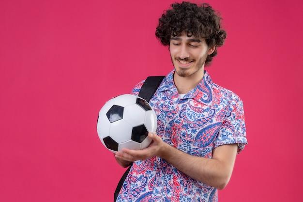 Sorridente giovane uomo riccio bello che tiene pallone da calcio e guardarlo sulla parete rosa isolata con lo spazio della copia
