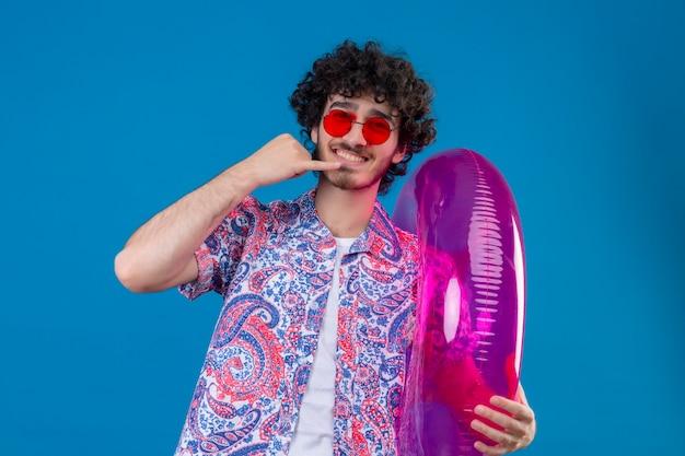 Sorridente giovane uomo riccio bello che indossa occhiali da sole che tengono l'anello di nuotata facendo gesto di chiamata sulla parete blu isolata