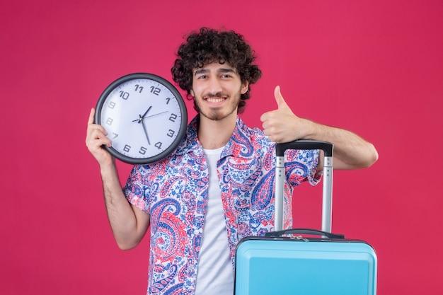 Sorridente giovane viaggiatore riccio bello uomo che tiene l'orologio che mostra pollice in alto mettendo la mano sulla valigia sulla parete rosa isolata