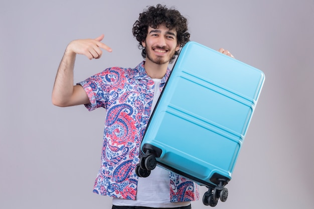 スーツケースを持って、孤立した白い壁にそれを指して笑顔の若いハンサムな巻き毛の旅行者の男