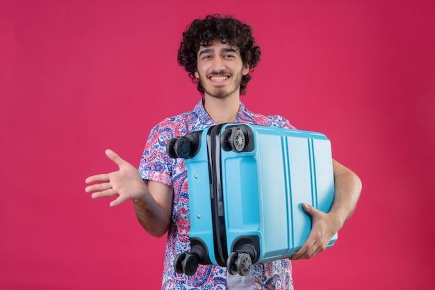 격리 된 분홍색 벽에 빈 손을 보여주는 가방을 들고 웃는 젊은 잘 생긴 곱슬 여행자 남자