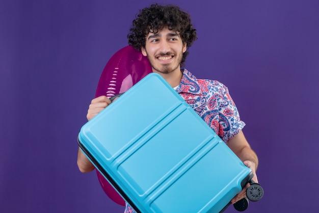 コピースペースと孤立した紫色の壁にスーツケースと水泳リングを保持している若いハンサムな巻き毛の旅行者の男性の笑顔
