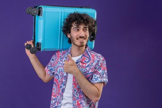 コピースペースと孤立した紫色の壁の右側を見て親指を上に表示肩にスーツケースを保持している若いハンサムな巻き毛の旅行者の男性の笑顔