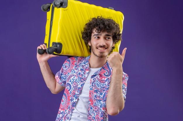 Sorridente giovane viaggiatore riccio bello uomo che tiene la valigia sulla spalla che mostra pollice in su guardando il lato destro sulla parete viola isolata con lo spazio della copia