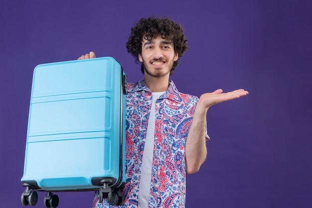 격리 된 보라색 벽에 빈 손을 보여주는 가방을 들고 웃는 젊은 잘 생긴 곱슬 여행자 남자