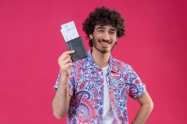 Sorridente giovane viaggiatore riccio bello uomo che tiene portafoglio e biglietti aerei sulla parete rosa isolata con lo spazio della copia