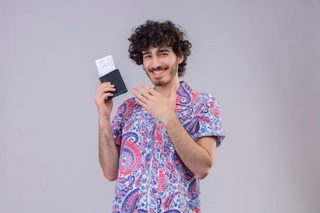 財布と飛行機のチケットを保持し、コピースペースのある孤立した白い壁に手でそれを指して若いハンサムな巻き毛の旅行者の男性を笑顔