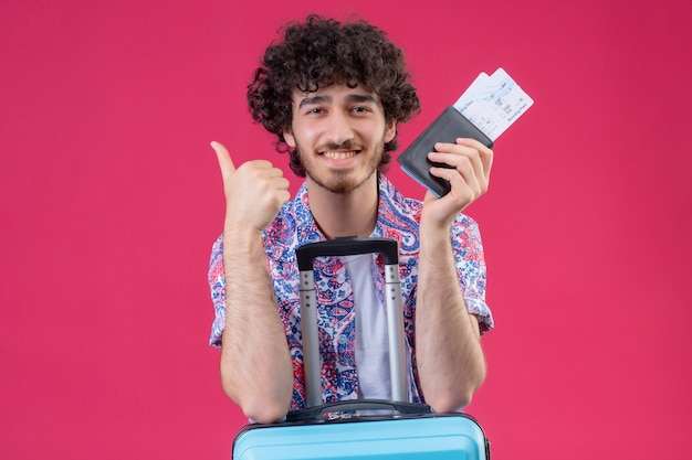 Улыбающийся молодой красивый кудрявый путешественник, держащий бумажник и билеты на самолет, кладет оружие на чемодан на изолированной розовой стене с копией пространства