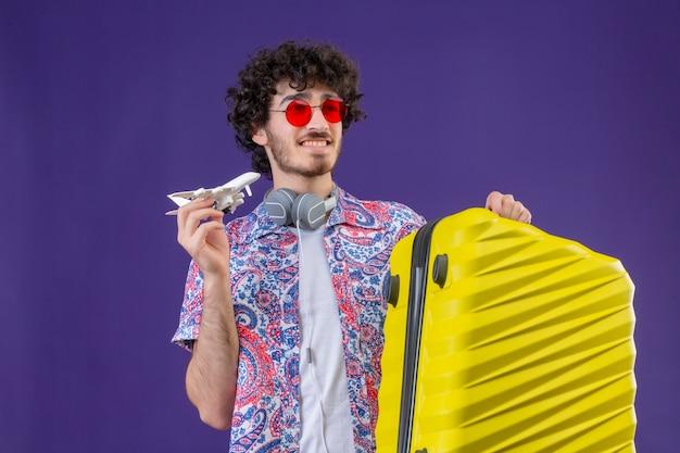 Sorridente giovane viaggiatore riccio bello uomo che indossa occhiali da sole che tengono la valigia e aereo modello sulla parete viola isolata con lo spazio della copia