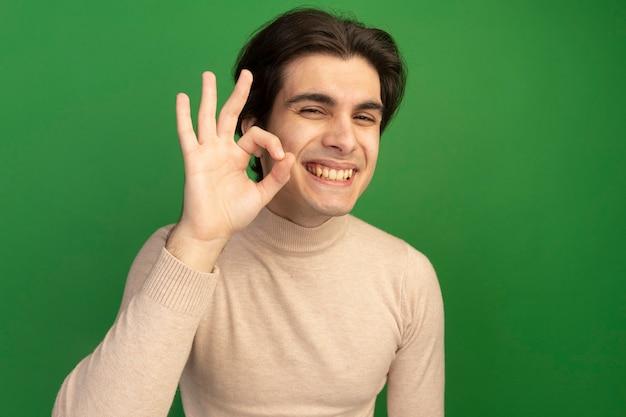Улыбающийся молодой красивый парень показывает нормальный жест, изолированный на зеленой стене