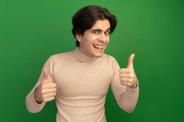 엄지 손가락에 고립 된 녹색 벽을 보여주는 웃는 젊은 잘 생긴 남자