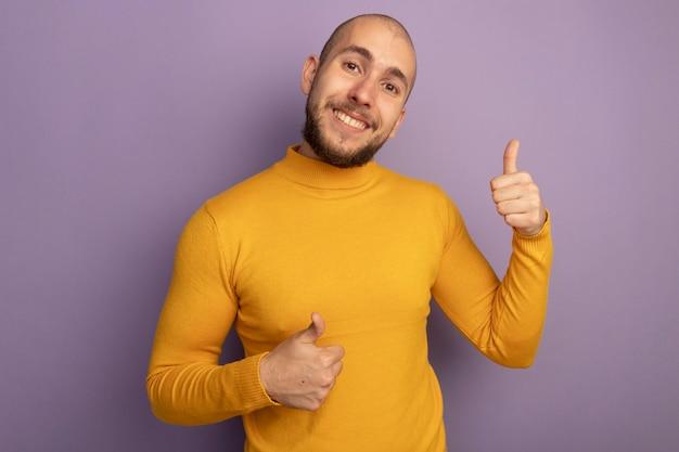 紫色の壁に分離された親指を示す笑顔の若いハンサムな男