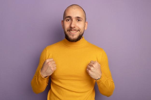 복사 공간이 보라색 벽에 고립 된 포즈 싸움에 서있는 젊은 잘 생긴 남자를 웃고
