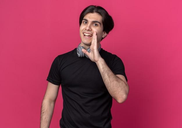 분홍색 벽에 고립 된 사람을 호출하는 목 주위에 검은 색 티셔츠와 헤드폰을 착용하는 젊은 잘 생긴 남자를 웃고