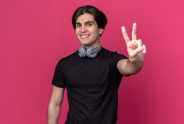 분홍색 벽에 고립 된 평화 제스처를 보여주는 목에 검은 색 티셔츠와 헤드폰을 착용하는 젊은 잘 생긴 남자를 웃고