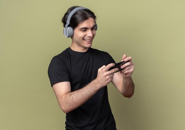 검은 티셔츠와 올리브 녹색 벽에 고립 된 전화 게임을하는 헤드폰을 입고 웃는 젊은 잘 생긴 남자