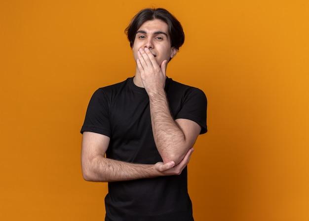 복사 공간 오렌지 벽에 고립 된 손으로 검은 티셔츠 덮여 입을 입고 웃는 젊은 잘 생긴 남자 무료 사진