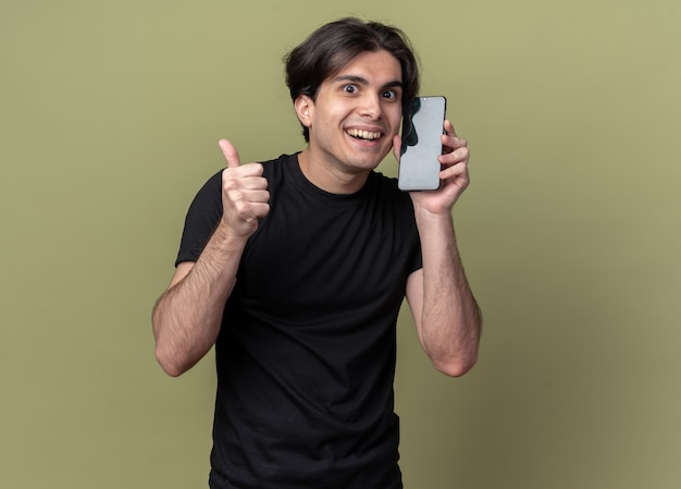 Smiling young handsome guy wearing black t-shirt holding alarm clock around face showing thumb up isolated on olive green wall