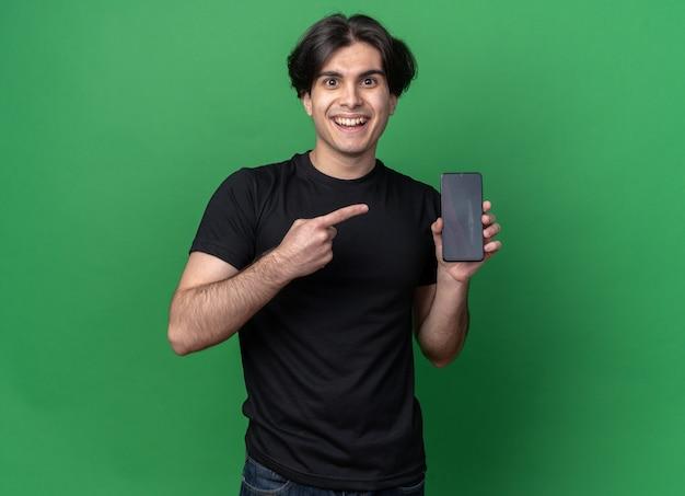 녹색 벽에 고립 된 전화에서 검은 티셔츠 지주와 포인트를 입고 웃는 젊은 잘 생긴 남자