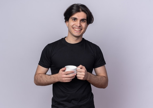 Smiling young handsome guy wearing black t-shirt holding cup of coffee isolated on white wall