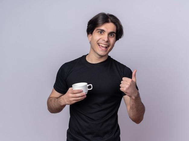 白い壁に分離された親指を示すコーヒーのカップを保持している黒いtシャツを着て笑顔の若いハンサムな男