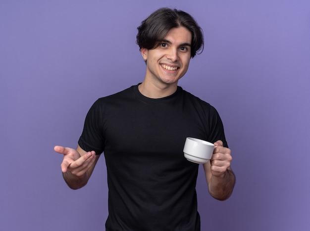 보라색 벽에 고립 된 제스처를 보여주는 커피 한잔 들고 검은 티셔츠를 입고 웃는 젊은 잘 생긴 남자