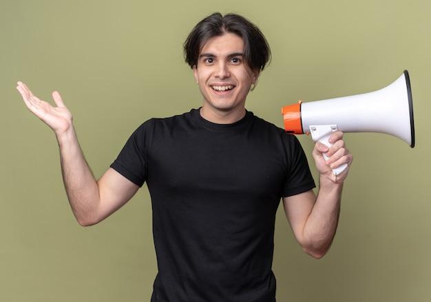 スピーカーを保持し、オリーブグリーンの壁に分離された手を広げて黒いtシャツを着て笑顔の若いハンサムな男