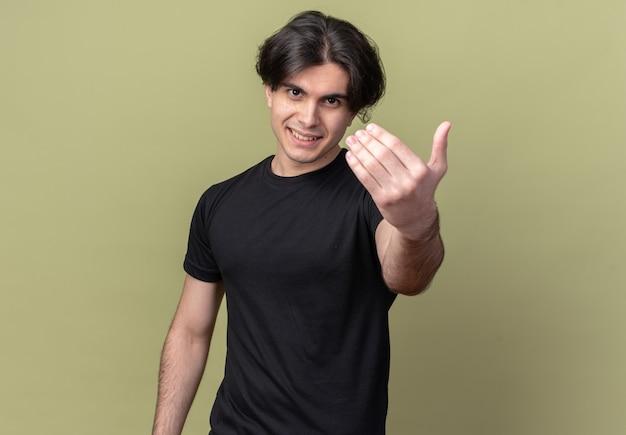올리브 녹색 벽에 고립 된 앞에 손을 들고 검은 티셔츠를 입고 웃는 젊은 잘 생긴 남자