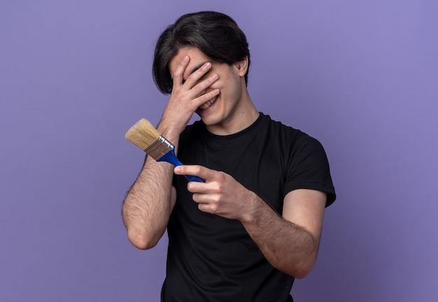 페인트 브러시를 들고 검은 티셔츠를 입고 웃는 젊은 잘 생긴 남자가 보라색 벽에 고립 된 손으로 얼굴을 덮었습니다.