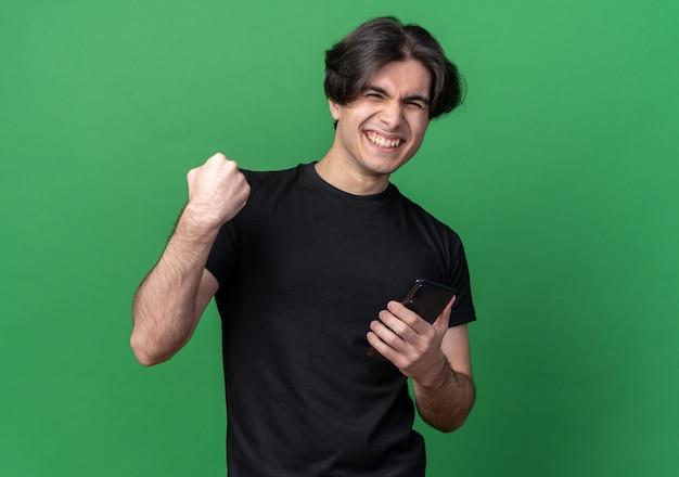 전화를 들고 검은 티셔츠를 입고 녹색 벽에 고립 된 예 제스처를 보여주는 젊은 잘 생긴 남자를 웃고