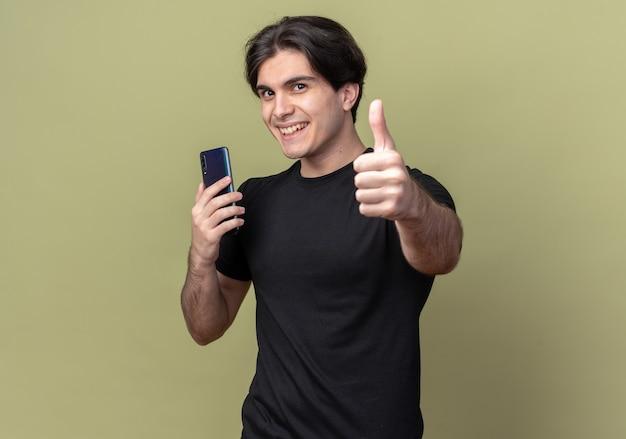 コピースペースとオリーブグリーンの壁に分離された親指を示す電話を保持している黒いtシャツを着て笑顔の若いハンサムな男