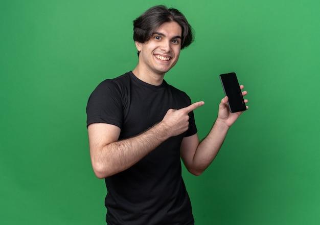 Sorridente giovane bel ragazzo che indossa la maglietta nera che tiene e punti al telefono isolato sulla parete verde