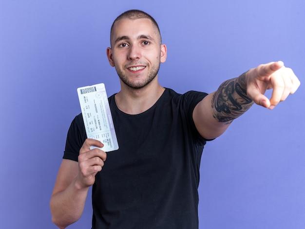 파란 벽에 격리된 앞 티켓 포인트를 들고 검은 티셔츠를 입은 웃고 있는 젊은 미남