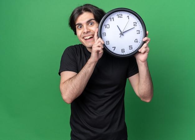 Sorridente giovane bel ragazzo che indossa t-shirt nera che tiene orologio da parete aroung faccia isolata sulla parete verde