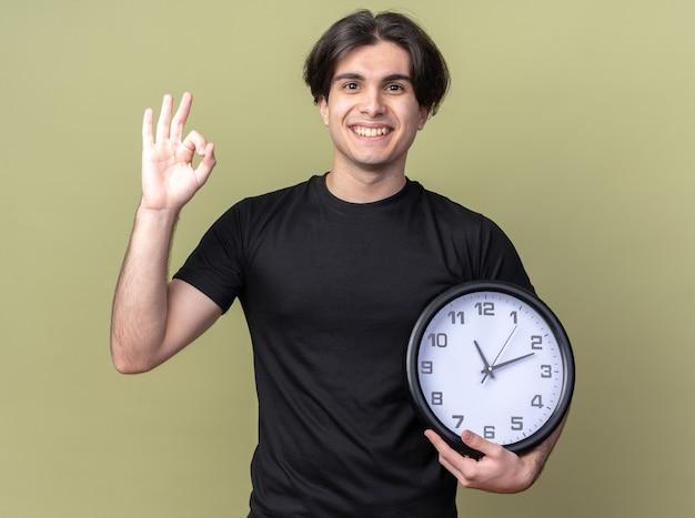 Sorridente giovane bel ragazzo che indossa la maglietta nera che tiene l'orologio da parete che mostra il gesto giusto isolato sulla parete verde oliva