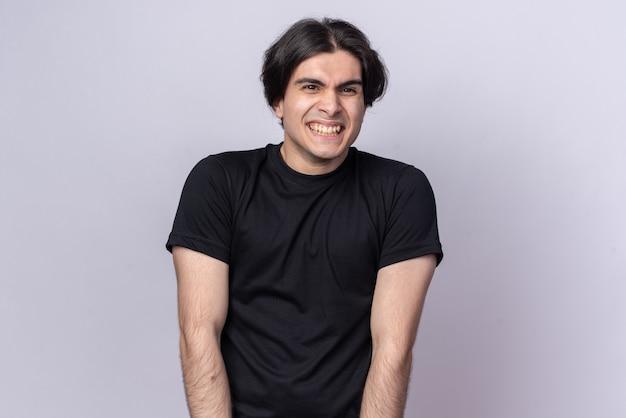 흰 벽에 고립 된 검은 티셔츠를 입고 웃는 젊은 잘 생긴 남자