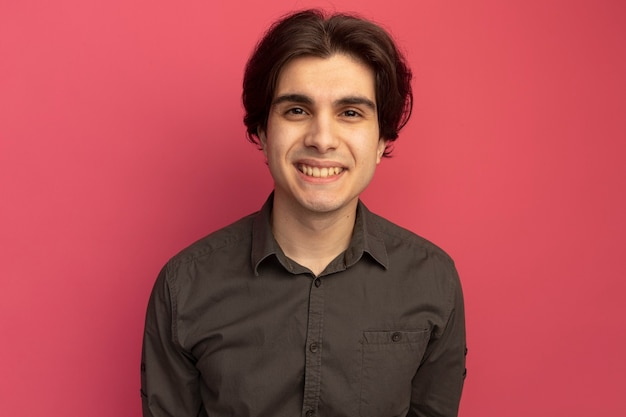 Smiling  young handsome guy wearing black t-shirt isolated on pink wall