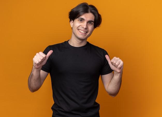 오렌지 벽에 고립 된 자신에 검은 티셔츠 포인트를 입고 웃는 젊은 잘 생긴 남자