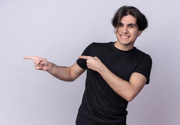 コピー スペースで白い壁に分離された側で黒の t シャツ ポイントを着ている若いハンサムな男の笑みを浮かべてください。