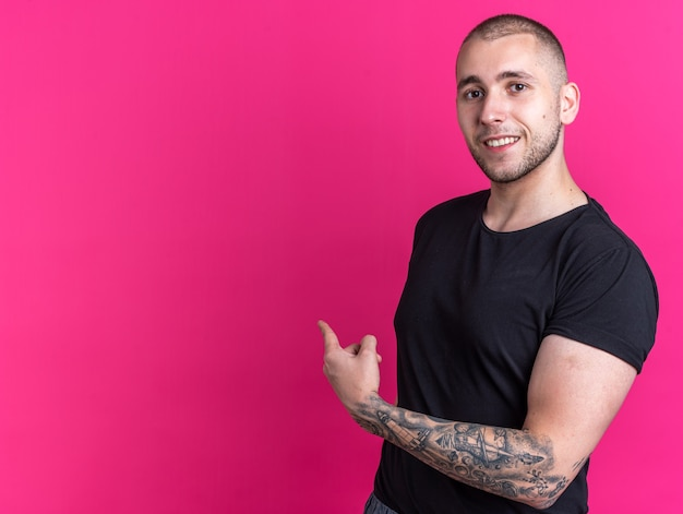 Smiling young handsome guy wearing black t-shirt points at behind isolated on pink wall with copy space