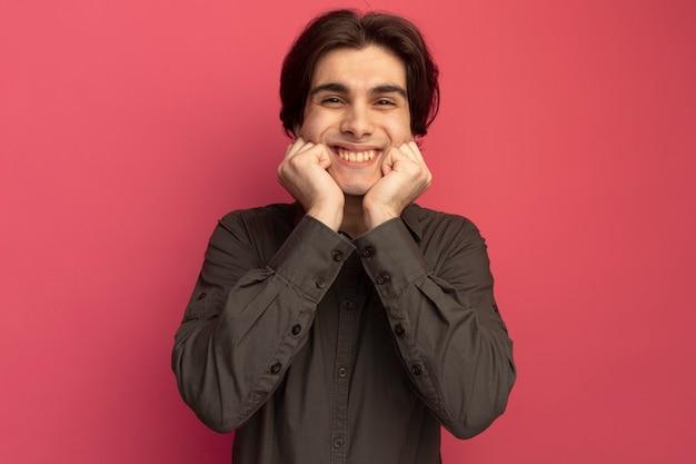 분홍색 벽에 고립 된 뺨에 손을 댔을 검은 티셔츠를 입고 웃는 젊은 잘 생긴 남자