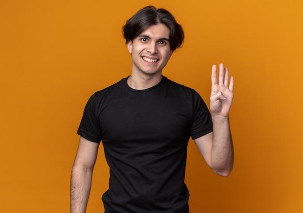 오렌지 벽에 고립 된 4를 보여주는 검은 티셔츠를 입고 웃는 젊은 잘 생긴 남자