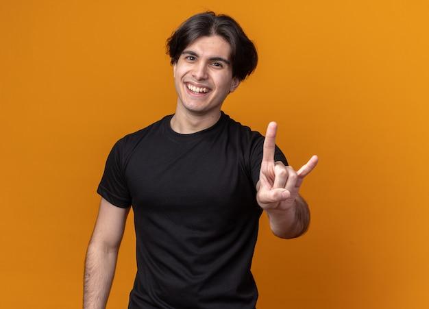 Улыбающийся молодой красивый парень в черной футболке показывает козлиный жест, изолированный на оранжевой стене