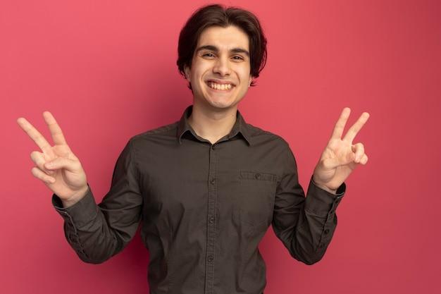 분홍색 벽에 고립 된 평화 제스처를 보여주는 검은 티셔츠를 입고 웃는 젊은 잘 생긴 남자