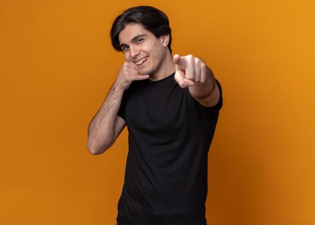 오렌지 벽에 고립 된 카메라에 전화 및 포인트를 보여주는 검은 티셔츠를 입고 웃는 젊은 잘 생긴 남자