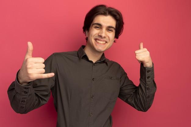 분홍색 벽에 고립 된 전화 제스처를 보여주는 검은 티셔츠를 입고 웃는 젊은 잘 생긴 남자