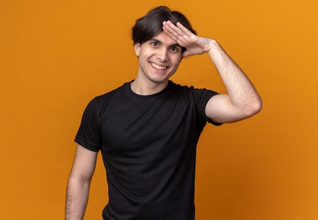 오렌지 벽에 고립 된 경례 제스처를 보여주는 검은 티셔츠를 입고 웃는 젊은 잘 생긴 남자