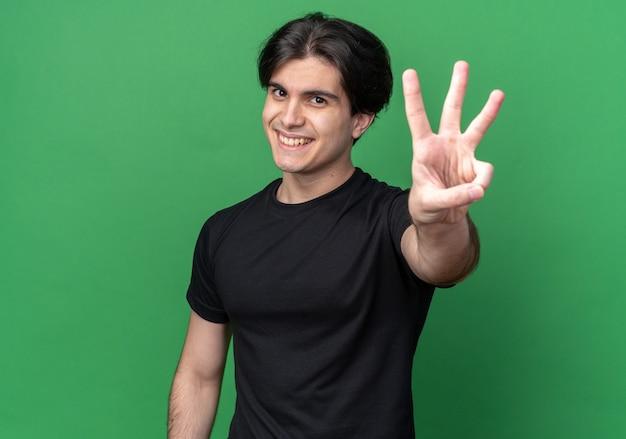 녹색 벽에 세 절연을 보여주는 검은 티셔츠를 입고 웃는 젊은 잘 생긴 남자