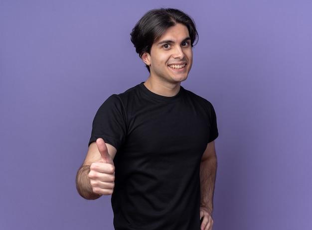 보라색 벽에 고립 된 엉덩이에 손을 넣어 엄지 손가락을 보여주는 검은 티셔츠를 입고 웃는 젊은 잘 생긴 남자
