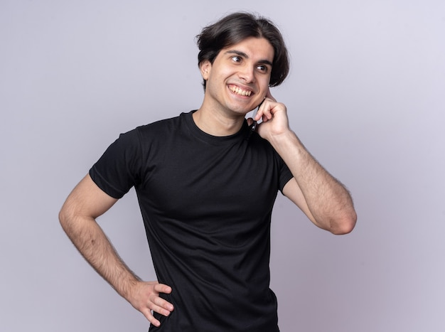 Smiling young handsome guy wearing black t-shirt speaks on phone putting hand on hip isolated on white wall